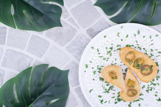 Fatias de pêra servidas com azeitonas verdes e ervas.