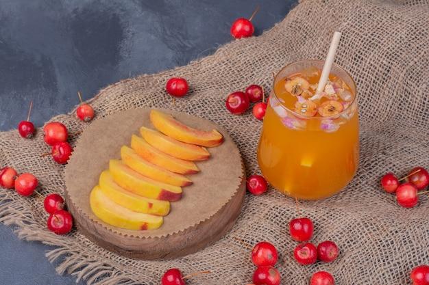Fatias de pêssego, cerejas e copo de suco de fruta em azul.
