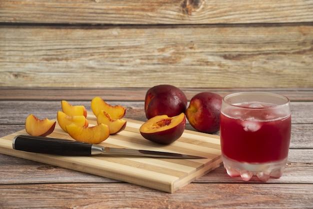 Fatias de pêssego em uma tábua de madeira com um copo de bebida gelada