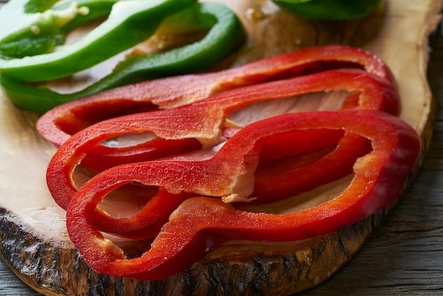 Fatias de pimenta verde e vermelha na placa de corte