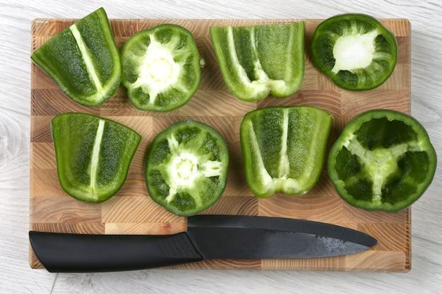 Fatias de pimentão com uma faca de cerâmica em uma placa de madeira. comida crua para cozinhar