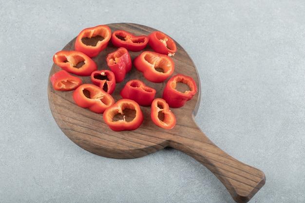 Fatias de pimentão doce em uma placa de madeira.