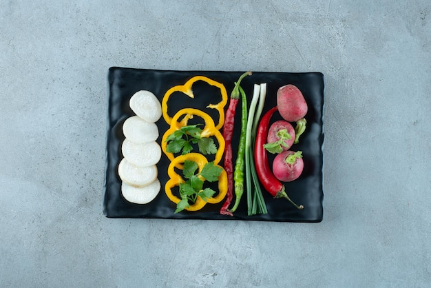 Fatias de pimentão, nabo, verduras e cebolas na chapa preta.