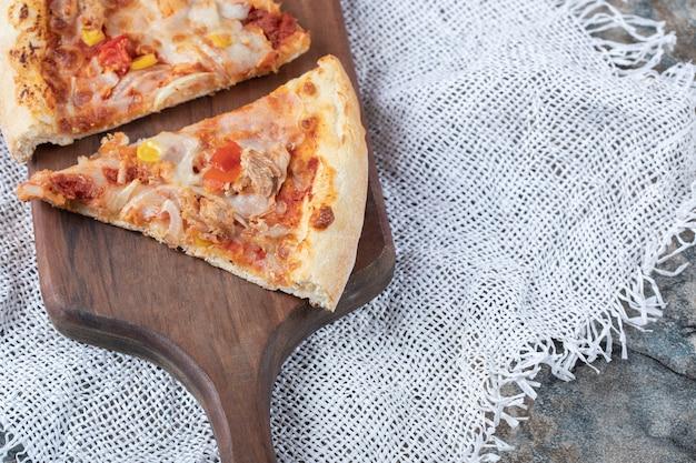 Fatias de pizza com queijo derretido no topo em uma placa de madeira sobre um pedaço de serapilheira branca