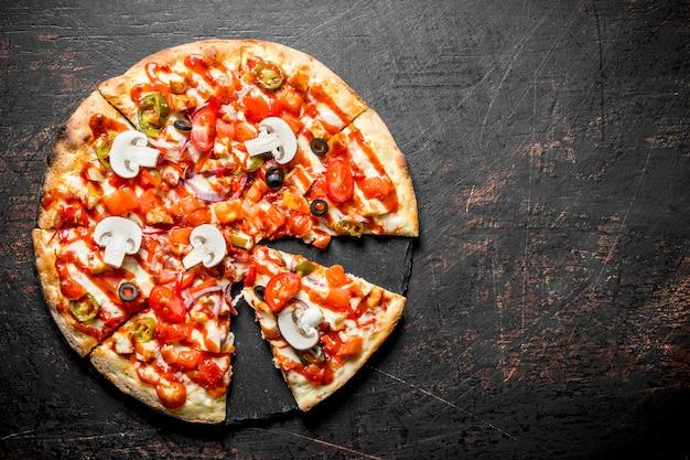 Fatias de pizza crocante com tomate, pimentão e cogumelos na mesa rústica escura.