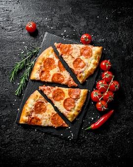 Fatias de pizza de calabresa com tomate e alecrim na mesa rústica preta.