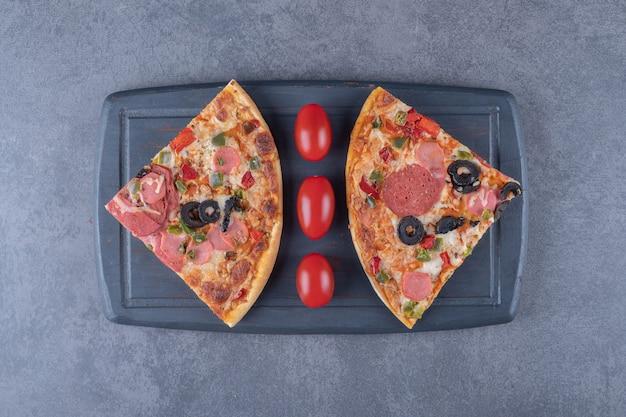 Fatias de pizza de calabresa fresca na placa de madeira.