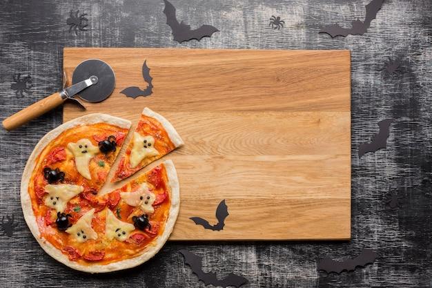 Fatias de pizza de halloween na placa de madeira