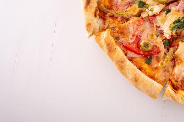 Fatias de pizza em madeira branca, copie o espaço, vista superior