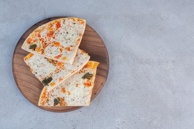 Fatias de pizza em uma placa de madeira com fundo de mármore.
