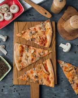 Fatias de pizza em uma placa de madeira de bambu