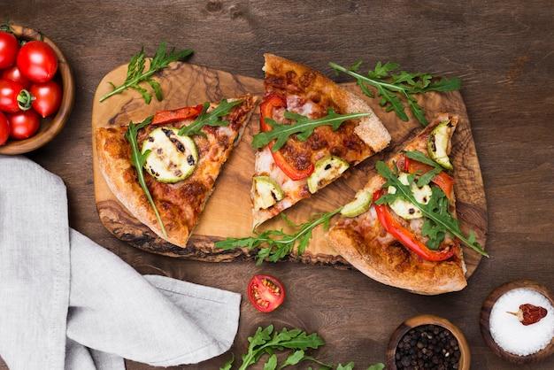 Fatias de pizza na placa de madeira acima vista