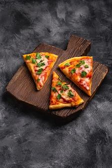 Fatias de pizza quente com queijo mussarela, presunto, tomate e salsa em uma tábua de madeira marrom, superfície de concreto de pedra, vista angular