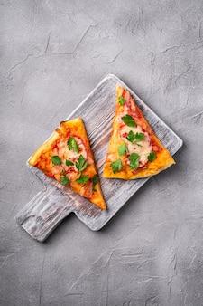 Fatias de pizza quente com queijo mussarela, presunto, tomate e salsa em uma tábua de madeira, superfície de concreto de pedra, vista superior