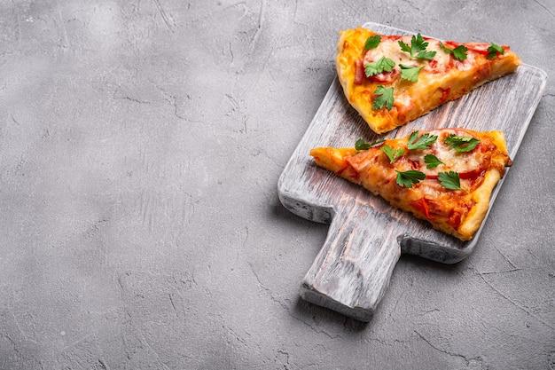 Fatias de pizza quente com queijo mussarela, presunto, tomate e salsa na tábua de madeira, concreto em pedra, ângulo, cópia, espaço para texto