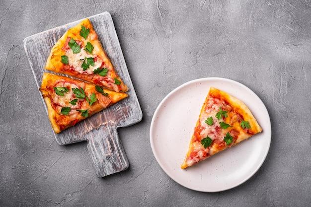 Fatias de pizza quente com queijo mussarela, presunto, tomate e salsa na tábua de madeira e na placa de pedra concreto vista superior do fundo