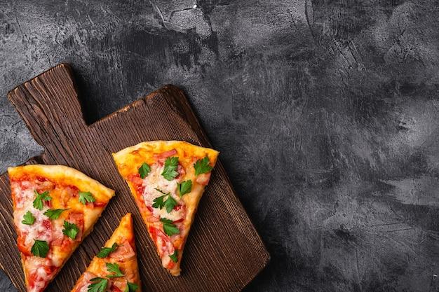 Fatias de pizza quente com queijo mussarela, presunto, tomate e salsa na tábua de madeira marrom pedra concreto fundo vista superior cópia espaço para texto