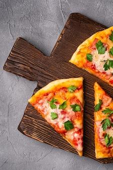 Fatias de pizza quente com queijo mussarela, presunto, tomate e salsa na tábua de madeira marrom, superfície de pedra de concreto, vista de cima de perto