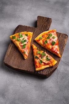 Fatias de pizza quente com queijo mussarela, presunto, tomate e salsa na tábua de madeira marrom vista de ângulo de fundo de concreto de pedra