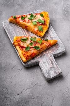 Fatias de pizza quente com queijo mussarela, presunto, tomate e salsa na tábua de madeira