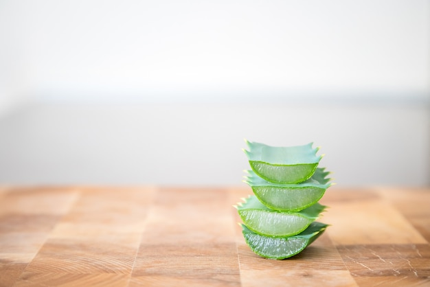 Fatias de plantas de aloe vera empilhadas umas sobre as outras em uma superfície de madeira.