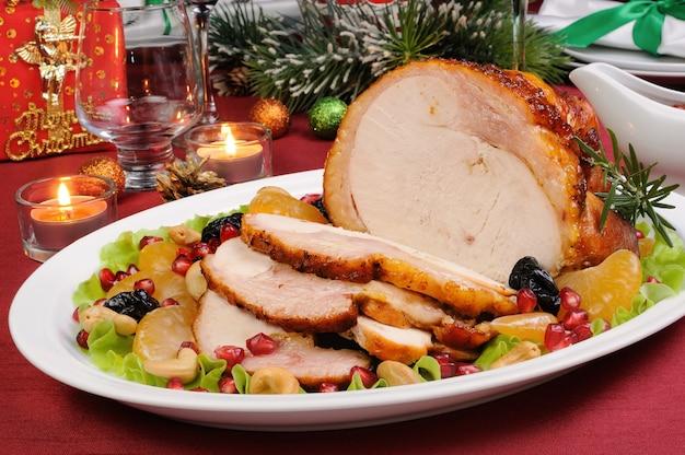 Fatias de presunto de peru assado com enfeite de frutas na mesa de natal