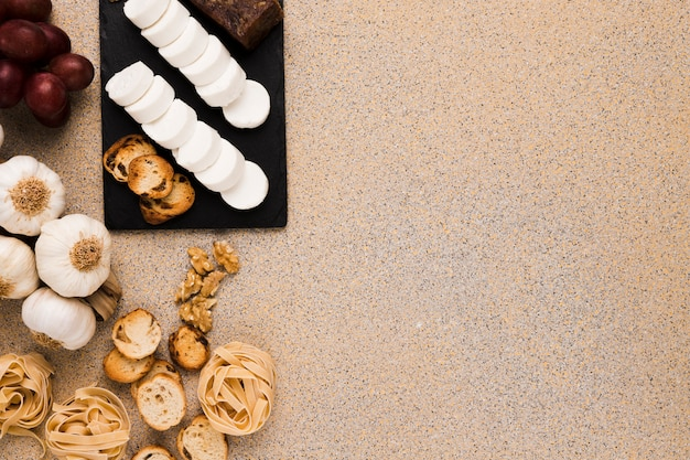 Fatias de queijo de cabra e pão na pedra ardósia preta com alimentos crus sobre mármore texturizado
