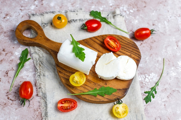 Fatias de queijo de cabra na placa de madeira com ruccola, tomate cereja. pronto para comer.