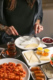 Fatias de queijo de corte de mulher servidas no café da manhã