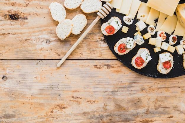 Fatias de queijo e aperitivo de pão com dipper mel na mesa de madeira