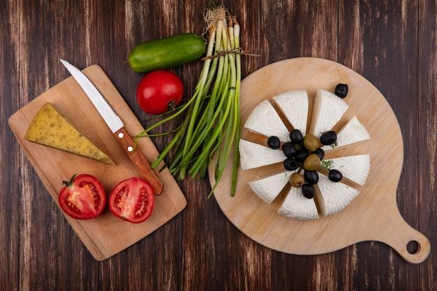 Fatias de queijo feta com azeitonas, tomates e uma faca em um suporte com pepino e cebolinha em um fundo de madeira.