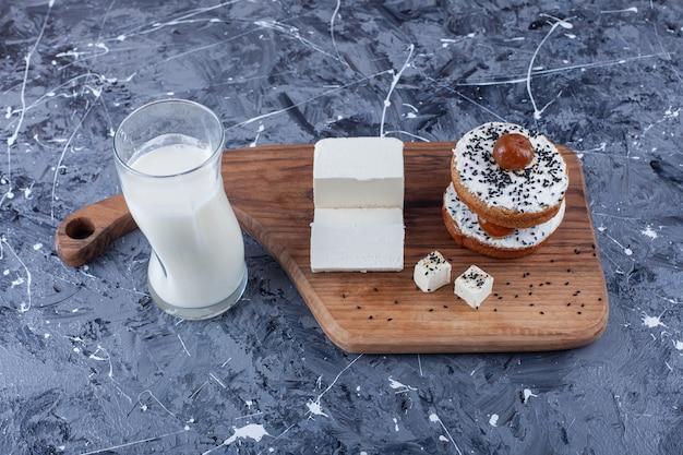 Fatias de queijo feta e pão de queijo em uma tábua ao lado de um copo de leite, na superfície azul.