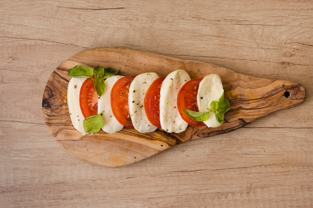 Fatias de queijo mussarela; tomates com erva na tábua contra o pano de fundo de madeira