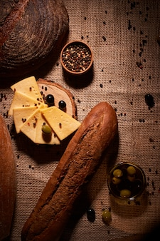 Fatias de queijo na mesa de madeira entre diferentes pães