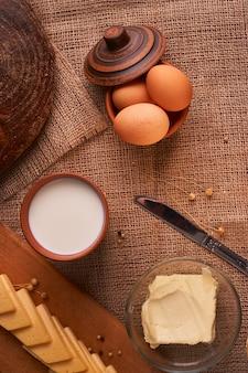 Fatias de queijo na mesa de madeira perto de baguete e leite