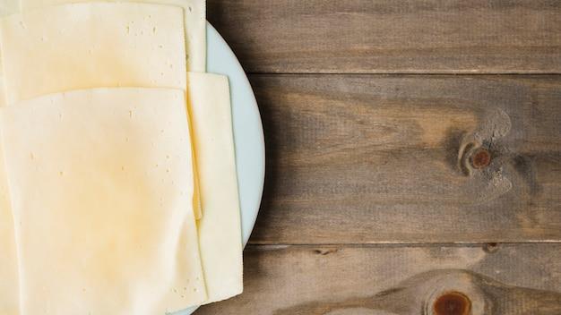 Fatias de queijo no prato branco contra o pano de fundo de prancha de madeira