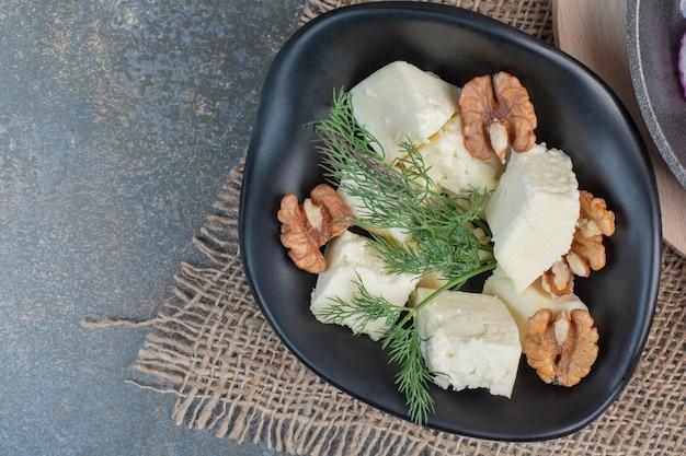 Fatias de queijo, sementes de endro e noz em uma tigela preta.