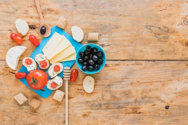 Fatias de queijo, tomate, pão e azeitonas na mesa de madeira