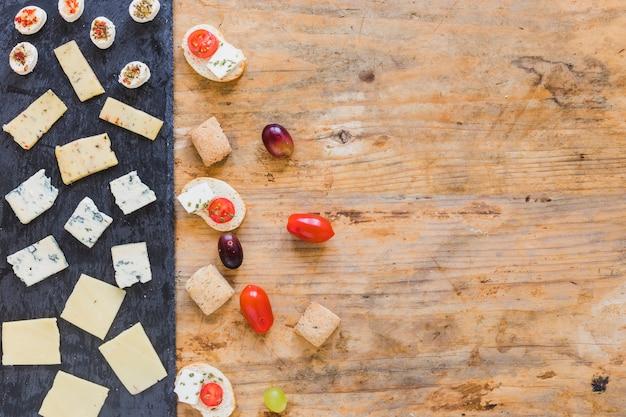 Fatias de queijo; tomates e uvas na superfície de madeira