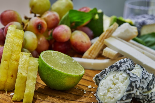 Fatias de queijos selecionados em uma placa de madeira com uvas, limão e abacaxi e ervas