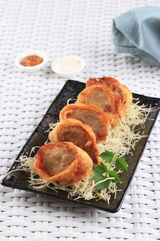 Fatias de rolinhos de ovo de frango, é ovo omelete recheado com frango moído e especiarias, cozido no vapor e frito, servido com molho de maionese de pimenta acima de vermicelli crocante
