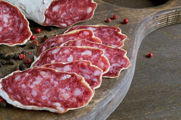 Fatias de salame francês seco com especiarias em fundo de madeira