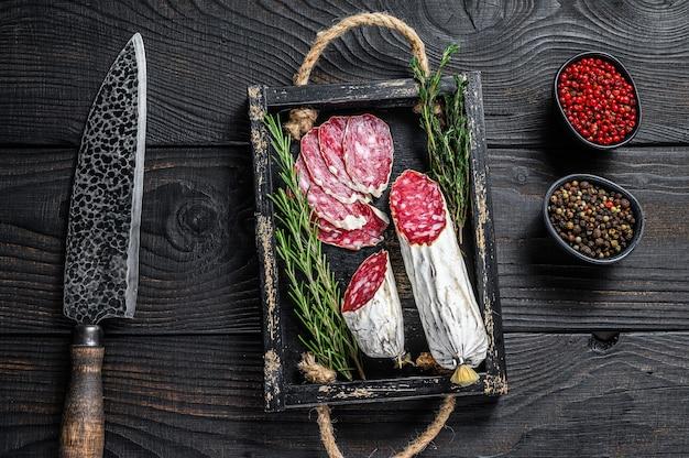 Fatias de salame salchichon curado seco em uma bandeja de madeira. fundo de madeira preto. vista do topo.
