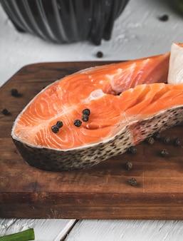 Fatias de salmão com bolas de pimenta preta em uma placa de madeira