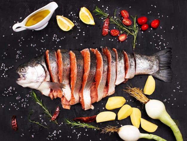 Fatias de salmão cru. peixe fresco com especiarias, tomate, cebola, limão, batata e azeite.