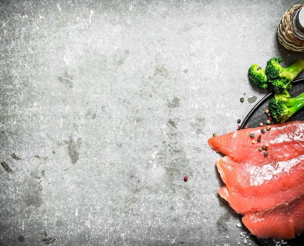 Fatias de salmão defumado com brócolis e sal no concreto.