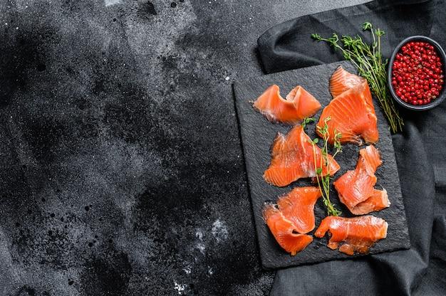 Fatias de salmão defumado com especiarias e ervas. peixe orgânico. fundo preto. vista do topo. copie o espaço