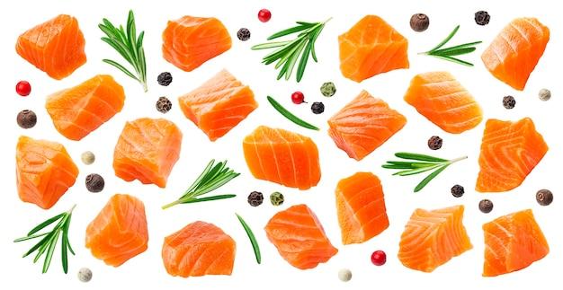 Fatias de salmão isoladas no fundo branco com traçado de recorte, cubos de peixe vermelho com alecrim e grãos de pimenta, ingrediente para sushi ou salada, macro