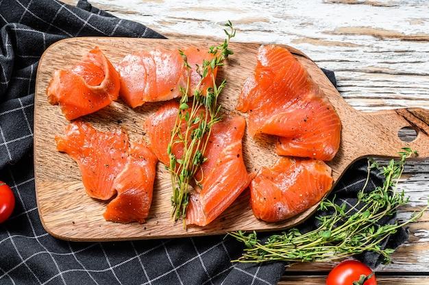 Fatias de salmão salgadas com pimenta e tomilho. peixe orgânico. fundo branco. vista do topo