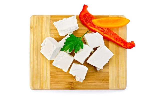 Fatias de salmoura queijo, salsa, fatias de pimentão vermelho e amarelo em uma placa de madeira isolada no fundo branco